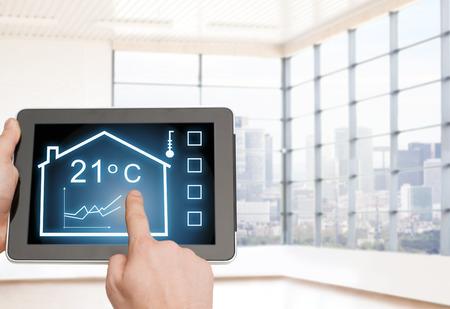 huis, huisvesting, mensen en technologie concept - close-up van de mens handen wijzende vinger naar tablet-pc computer en het reguleren kamertemperatuur over lege flat achtergrond