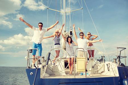 persona viajando: vacaciones, viaje, mar, la amistad y la gente conceptuales - sonriendo amigos sentados en la cubierta del yate y un saludo Foto de archivo