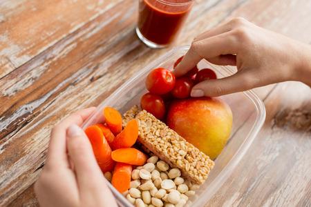 personas saludables: la alimentación saludable, la dieta y el concepto de la gente - cerca de la mujer de las manos con los alimentos en un recipiente de plástico y jugo de tomate fresco en la cocina de la casa
