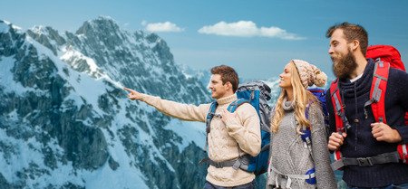 アドベンチャー、旅行、観光、ハイキング、人々 の概念 - アルプス山脈の背景の上の指を指しているバックパックと笑顔の友達のグループ 写真素材