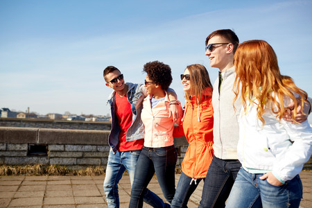 people together: tourism, travel, people and leisure concept - group of happy teenage friends walking along city street and talking