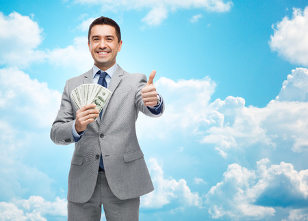 business, people and finances concept - smiling businessman with dollar money showing thumbs up over blue sky with clouds background