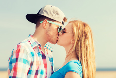 young couple hugging kissing: holidays, vacation and love concept - teenage couple kissing outdoors