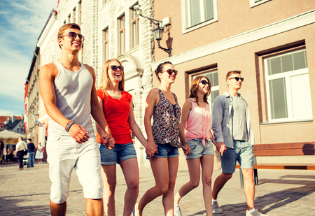 friendship, leisure, summer, gesturer and people concept - group of smiling friends walking and holding hands in city