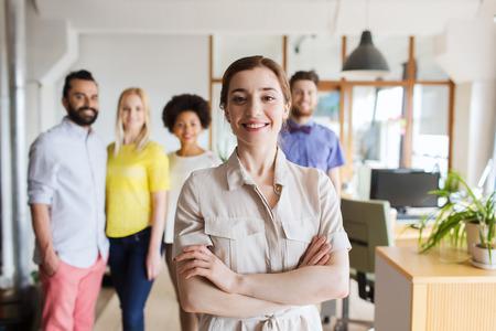 bedrijf, opstarten, mensen en teamwork concept - happy jonge vrouw over creatieve team in kantoor Stockfoto