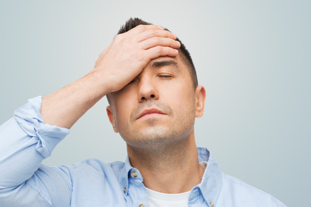 male headache: stress, headache, health care and people concept - unhappy man with closed eyes touching his forehead over gray background