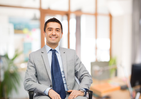 mid adult male: business, people and office concept - happy businessman in suit sitting in chair over office room background