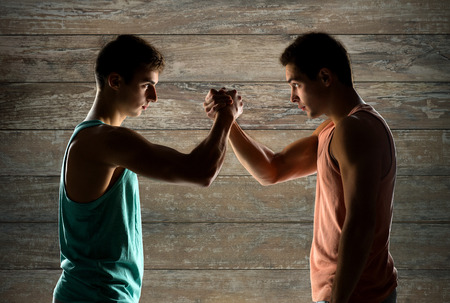 opponents: sport, competition, strength and people concept - two young men arm wrestling over wooden wall background
