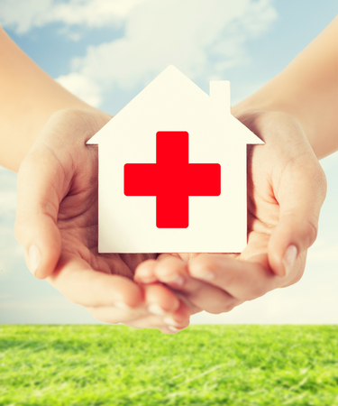 red cross: healthcare, medicine and charity concept - hands holding white paper house with red cross sign