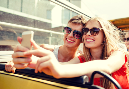 making love: friendship, tourism, summer vacation, technology and people concept - smiling couple with smartphone traveling by tour bus and making selfie
