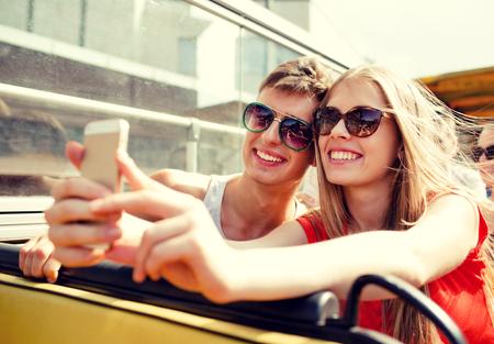 haciendo el amor: la amistad, el turismo, las vacaciones de verano, la tecnología y el concepto de la gente - sonriente pareja con itinerante teléfono inteligente en un autobús turístico y haciendo selfie