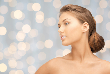 looking aside: beauty, people, holidays, luxury and health concept - beautiful young woman face looking aside over lights background