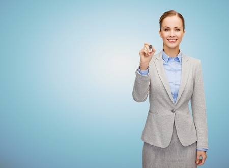 business, people and education concept - smiling young businesswoman writing something imaginary over blue background Banco de Imagens