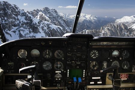 air transport, travel, technology and aviation concept - dashboard in airplane cockpit and view of snowy alps mountains behind windshield Stock Photo
