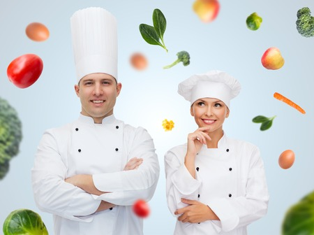 woman diet: cooking, profession, vegetarian diet and people concept - happy chef couple or cooks over blue background with falling vegetables