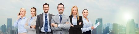 bedrijfsleven, mensen, gebaar en office concept - groep van lachende zakenmensen over de stad achtergrond