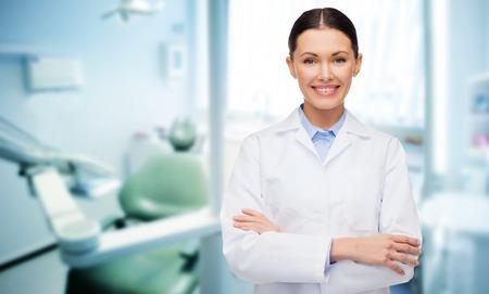 gente, medicina, estomatología y el concepto de salud - dentista feliz de mujer joven con las herramientas más de fondo de la oficina médica