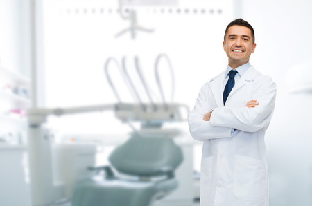 cuidado de la salud, profesión, estomatología y el concepto de la medicina - varón sonriente dentista de mediana edad sobre fondo consultorio médico Foto de archivo
