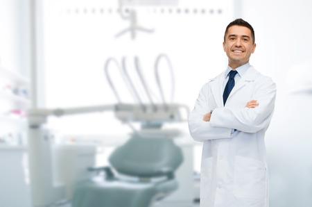 odontologia: cuidado de la salud, profesión, estomatología y el concepto de la medicina - varón sonriente dentista de mediana edad sobre fondo consultorio médico