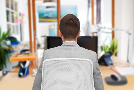 view of an elegant office: business, people, furniture, rear view and office concept - businessman sitting in chair from back over office room background Stock Photo
