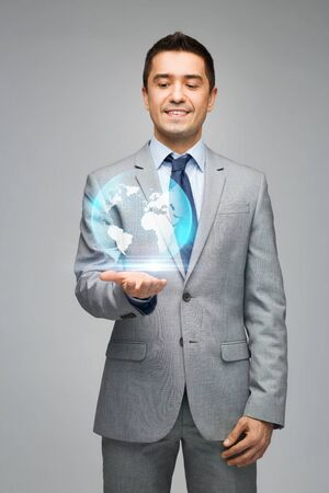 gray suit: business, people, technology and global communication concept - happy businessman in suit showing globe hologram over gray background