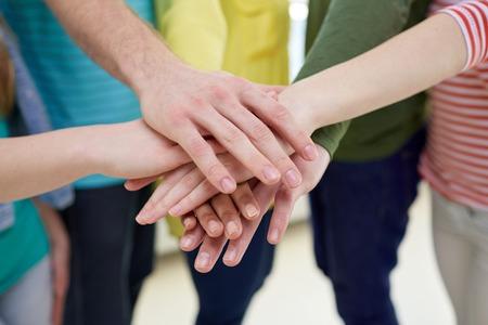 manos juntas: la educación, la escuela, la gente, la amistad y el trabajo en equipo concepto - cerca de los estudiantes o amigos con las manos en la parte superior sentados en la escalera Foto de archivo