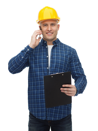 builder: repair, building, construction and maintenance concept - smiling man or builder in helmet with clipboard calling on smartphone