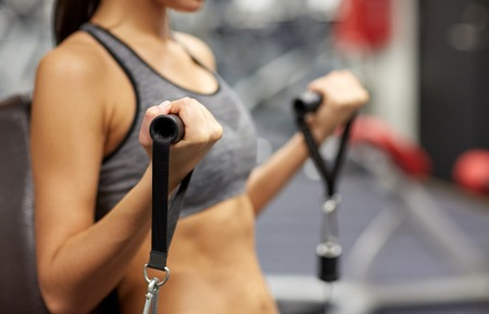 woman working out: sport, fitness, lifestyle and people concept - close up of young woman flexing muscles on cable gym machine Stock Photo