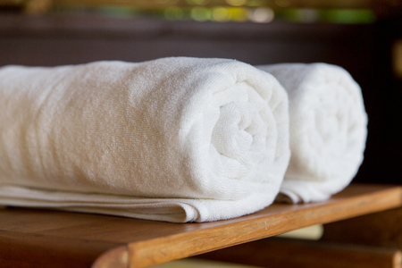 fold: luxury and hygiene concept - rolled bath towels at hotel spa