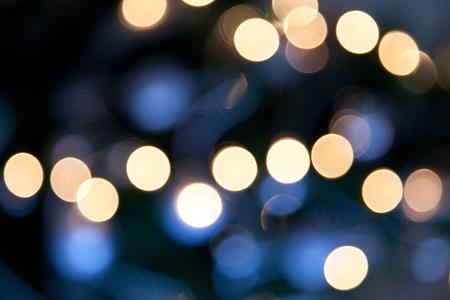Światła: holidays, illumination and electricity concept - colorful bright lights on dark blue night background