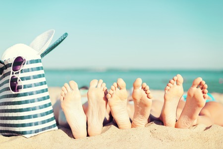 summer vacation, sunbathing and pedicure concept - three women lying on the beach with straw hat, sunglasses and bag 스톡 콘텐츠