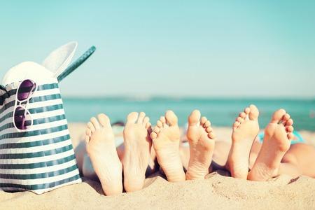 verano: vacaciones de verano, tomar el sol y pedicura concepto - tres mujeres tumbado en la playa con sombrero de paja, gafas de sol y el bolso