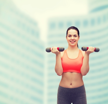 hispanic woman: sport, exercising and healthcare concept - young sporty woman with light dumbbells Stock Photo