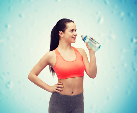 girl in sportswear: sport, exercise and healthcare - sporty woman with water bottle
