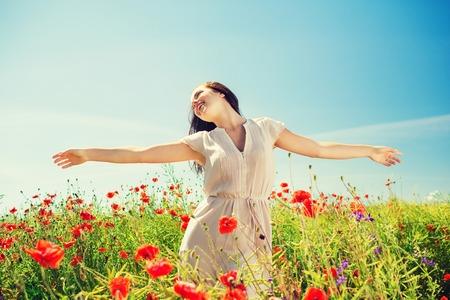 champ de fleurs: bonheur, nature, été, les vacances et les gens notion - souriante jeune femme sur le champ de pavot