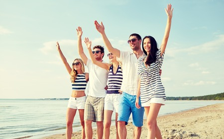 family outside: summer, holidays, sea, tourism and people concept - group of smiling friends in sunglasses walking on beach and waving hands