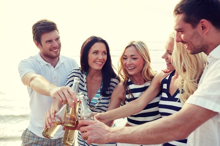 cider: summer, holidays, tourism, drinks and people concept - group of smiling friends clinking bottles of beer or cider on beach