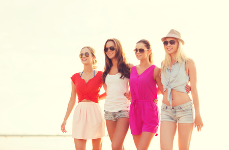 women smiling: summer vacation, holidays, travel and people concept - group of smiling young women in sunglasses and casual clothes on beach