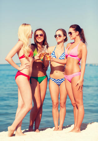 girls in bikini: summer vacation, holidays, travel and people concept - group of smiling young women sunbathing and drinking on beach