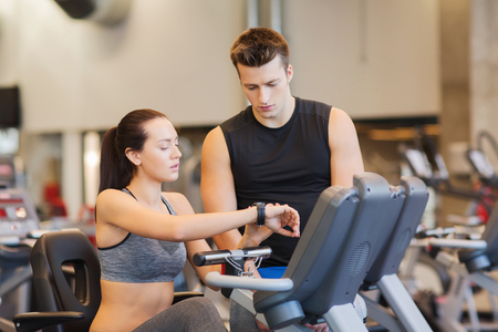 man gym: sport, fitness, lifestyle, technology and people concept - woman with trainer working out on exercise bike in gym