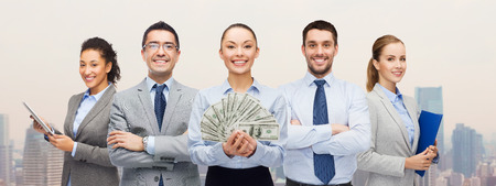 building loan: business, success and finances concept - group of smiling business people with dollar cash money over city background
