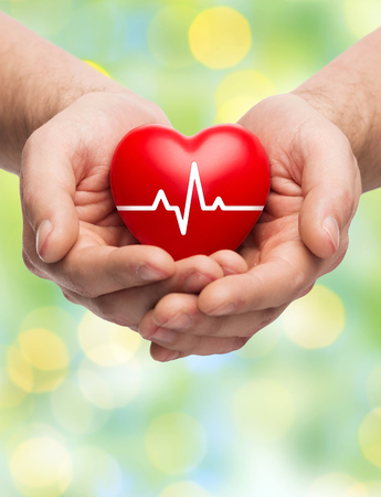 hand care: family health, charity and medicine concept - close up of hands holding red heart with cardiogram over green lights background