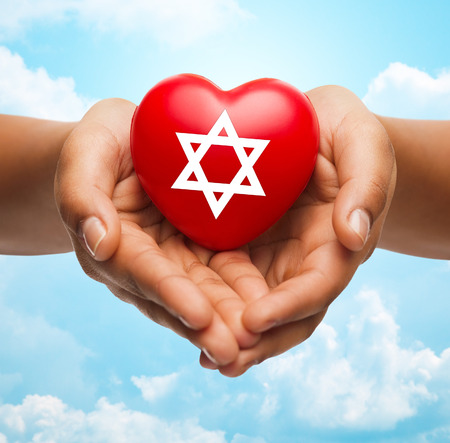 jewish star: religion, christianity, jewish community and charity concept - close up of female hands holding red heart with star of david symbol over blue sky and clouds background