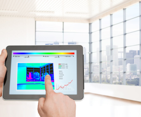 regulating: home, housing, people and technology concept - close up of man hands pointing finger to tablet pc computer and regulating room temperature over empty flat background