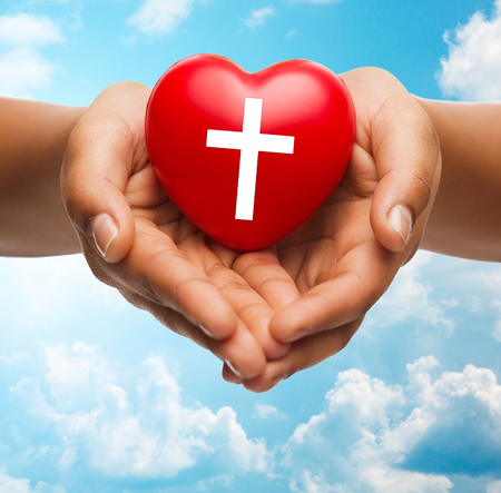 hands holding heart: religion, christianity and charity concept - close up of female hands holding red heart with christian cross symbol over blue sky and clouds background