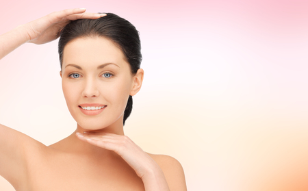 beige background: beauty, people and health concept - beautiful young woman touching her face and chin over pink background Stock Photo