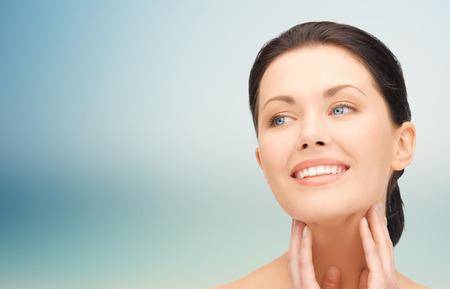 caras: la belleza, la gente y el concepto de salud - mujer hermosa joven tocando la cara y el cuello sobre fondo azul Foto de archivo