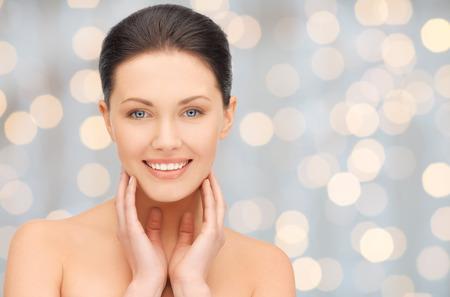 visage: la beauté, les gens, les vacances, le luxe et le concept de santé - belle jeune femme de toucher son visage et le cou sur les lumières de fond