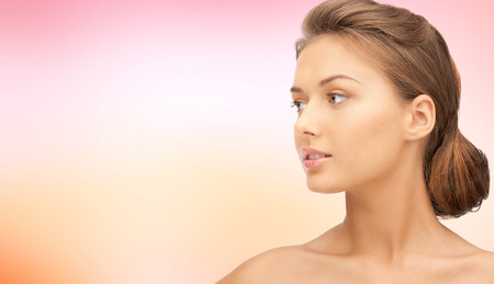 looking aside: beauty, people and health concept - beautiful young woman face looking aside over pink background Stock Photo
