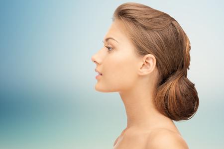 profil: zdrowie, ludzie, chirurgia plastyczna i koncepcja piękna - piękna młoda kobieta twarz na niebieskim tle